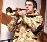 Colour picture of Mark Rice Oxley as Borachio playing the trumpet, act five, scene three.